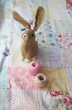 Haren och tråden på en patchworkbakgrund Arkivfoto