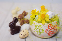 Hares, chocolate eggs in the decorative nest decorated with daff Stock Images