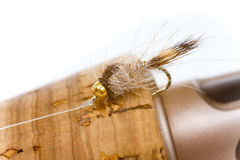 Hares Ear Nymph on Fly Rod. Isolated in a studio with a white background a hares ear nymph in natural colors is photographed closeup against the cork handle of a Stock Images