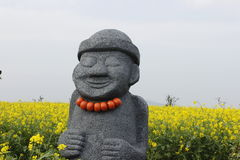 Hareubang black stone statue with yellow  in Jeju island Korea. Hareubang black stone statue with yellow background in Jeju island Korea Stock Photo