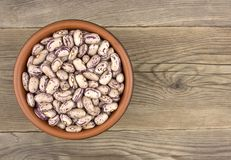 Haricot beans in bowl on wooden background. Haricot beans in ceramic bowl on wooden table. Top view Royalty Free Stock Image