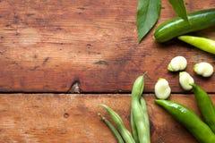 Haricot vert, bondbönabasilikasidor och gröna chili på en ru arkivfoto