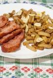 Haricot vert med skivor av stekt bacon och som dekorerar med skivor av vitlök på den vita plattan på dekorerad bordduk Arkivbilder
