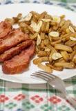 Haricot vert med skivor av stekt bacon och som dekorerar med skivor av vitlök på den vita plattan på dekorerad bordduk Arkivfoton