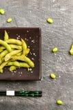 Haricot vert på en brun platta med pinnar, sikten uppifrån Royaltyfri Foto