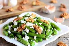 Haricot vertsalladrecept Läcker haricot vertsallad med keso, valnötter, vitlök och kryddor på en platta Arkivbild