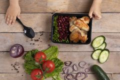 Haricots bouillis rouges avec les ailes de poulet grillées, légumes crus autour, mains d'enfants photos stock