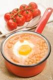 Haricots cuits au four avec l'oeuf au plat dans un pot rouge d'émail Image stock