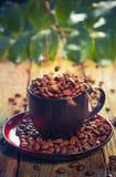 Haricots de Brown versant la tasse de café Image stock