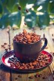 Haricots de Brown versant la tasse de café Photo libre de droits