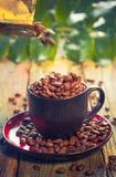 Haricots de Brown versant la tasse de café Photographie stock libre de droits