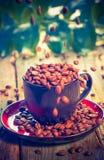Haricots de Brown versant la tasse de café Photographie stock
