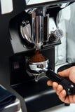 Haricots de cafè fraîchement moulu dans un portafilter par la broyeur de café image libre de droits