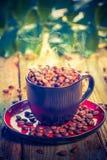 Haricots de café chaud noir de tasse pleins Photos stock