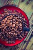 Haricots de café noir de tasse pleins Photo stock