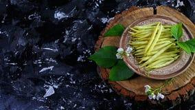 Haricots jaunes d'asperge d'un plat d'argile, sur le tronçon en bois, fond foncé Recette de nourriture sur le fond en bois Vue de images stock