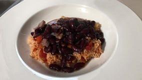 Haricots nains et saucisse ladled au-dessus du riz espagnol banque de vidéos