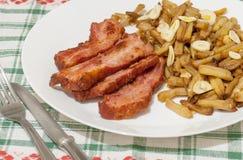 Haricots verts avec des tranches de lard frit et décorées des tranches d'ail du plat blanc sur la nappe décorée Images stock