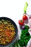 Haricots verts avec le souce de lobio de tomates dans la poêle sur le fond blanc photographie stock libre de droits