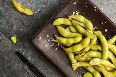 Haricots verts d'un plat brun avec des baguettes, la vue à partir du dessus Image libre de droits