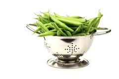 Haricots verts dans une passoire en métal photos stock