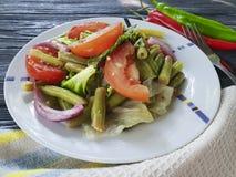 Haricots verts de salade, tomate, organique une laitue gastronome en bois, épices appétissantes de déjeuner de poivre de pain photo libre de droits