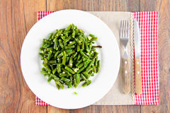 Haricots verts frits avec l'ail d'un plat blanc photo stock