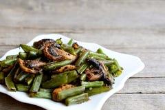 Haricots verts rôtis avec des champignons et des épices d'un plat et sur le vieux fond en bois avec l'espace de copie pour le tex photos stock