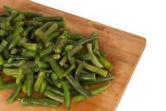 Haricots verts verts sur un conseil en bois Photo stock