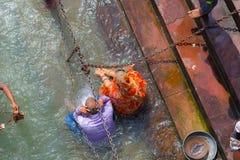 Haridwar, Índia - 11 de março de 2017: povos não identificados que banham e que tomam abluções no Ganges River nos ghats santamen Imagens de Stock