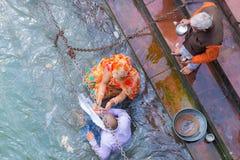 Haridwar, Índia - 11 de março de 2017: povos não identificados que banham e que tomam abluções no Ganges River nos ghats santamen Fotografia de Stock