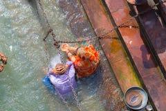 Haridwar, Índia - 11 de março de 2017: povos não identificados que banham e que tomam abluções no Ganges River nos ghats santamen Imagens de Stock Royalty Free