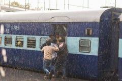Haridwar, India - Maart 11, 2017: Menigte het inschepen trein in Haridwar-station onder zware moessonregen Jonge jongens die t be stock foto's