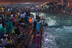 Haridwar, India - March 20, 2017: Holy ghats at Haridwar, India, sacred town for Hindu religion. Pilgrims offering floating flowe Royalty Free Stock Photo