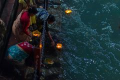 Haridwar, India - March 20, 2017: Holy ghats at Haridwar, India, sacred town for Hindu religion. Pilgrims offering floating flowe Royalty Free Stock Images