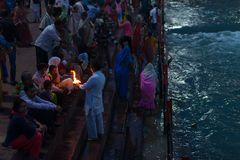 Haridwar, India - March 20, 2017: Holy ghats at Haridwar, India, sacred town for Hindu religion. Pilgrims offering floating flowe Royalty Free Stock Image