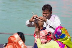 Haridwar, India - March 20, 2017: Man shaving off hairs for young Hindu devotee initiation on the Ganges River at Haridwar, India. Stock Image