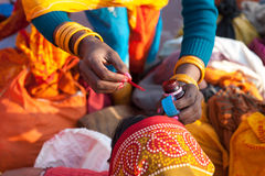 Painting the bindi on woman's face after bath in Ganges Royalty Free Stock Photography