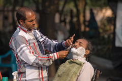 Haridwar, India. HARIDWAR, INDIA - NOVEMBER 8, 2012: An unidentified street barber shaving a man using an open razor blade on a bank of sacred river Ganges in Royalty Free Stock Image