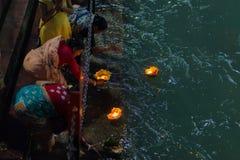 Haridwar Indien - mars 20, 2017: Heliga ghats på Haridwar, Indien, sakral stad för hinduisk religion Pilgrims som erbjuder sväva  Arkivbild