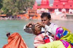 Haridwar Indien - mars 20, 2017: Man att raka av hår för ungt hinduiskt fantastpåbörjande på Gangeset River på Haridwar, Indien Royaltyfri Foto