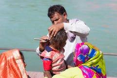 Haridwar Indien - mars 20, 2017: Man att raka av hår för ungt hinduiskt fantastpåbörjande på Gangeset River på Haridwar, Indien Fotografering för Bildbyråer