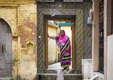 HARIDWAR, LA INDIA - 23 DE MARZO DE 2014: mujer india que lleva la sari colorida en la entrada fotografía de archivo libre de regalías