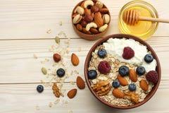 harina de avena, arándanos, frambuesas, miel y nueces sanos del desayuno en la tabla de madera blanca Visión superior con el espa Imágenes de archivo libres de regalías