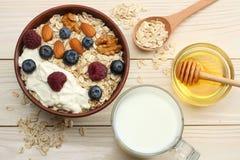 harina de avena, arándanos, frambuesas, miel y nueces sanos del desayuno en la tabla de madera blanca Visión superior con el espa Imagenes de archivo