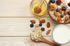 harina de avena, arándanos, frambuesas, miel y nueces sanos del desayuno en la tabla de madera blanca Visión superior con el espa Fotos de archivo libres de regalías