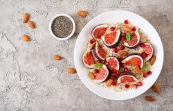 Harina de avena deliciosa y sana con los higos, la almendra y las semillas del chia fotografía de archivo