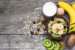 Harina de avena en un cuenco con las frutas, las nueces y las bayas con una cuchara Desayuno sano Imagenes de archivo