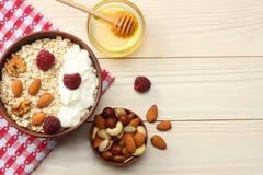harina de avena, frambuesas, miel y nueces sanas del desayuno en la tabla de madera blanca Visión superior con el espacio de la c Imagen de archivo libre de regalías