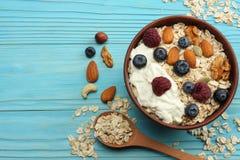 harina de avena, miel, arándanos, frambuesas y nueces sanos del desayuno en la tabla de madera azul Visión superior con el espaci Imagen de archivo